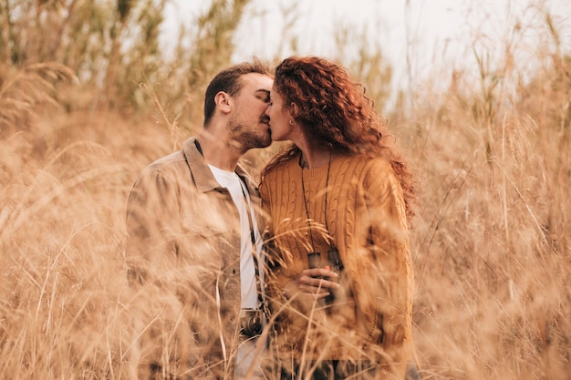Vista frontal pareja besándose en el campo de trigo