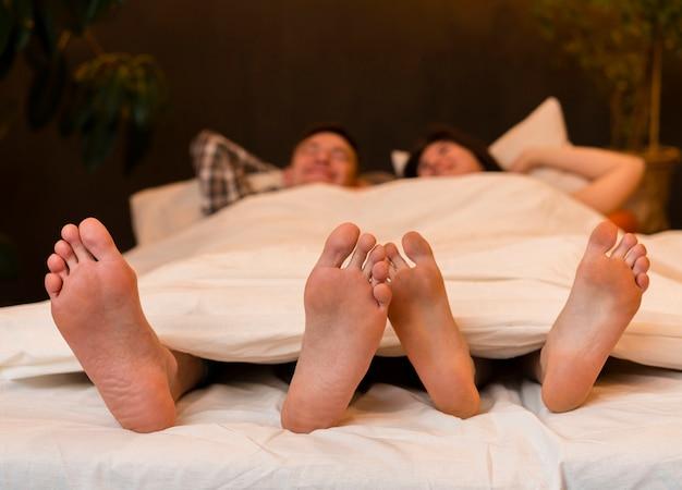 Vista frontal de la pareja en la cama descalzo