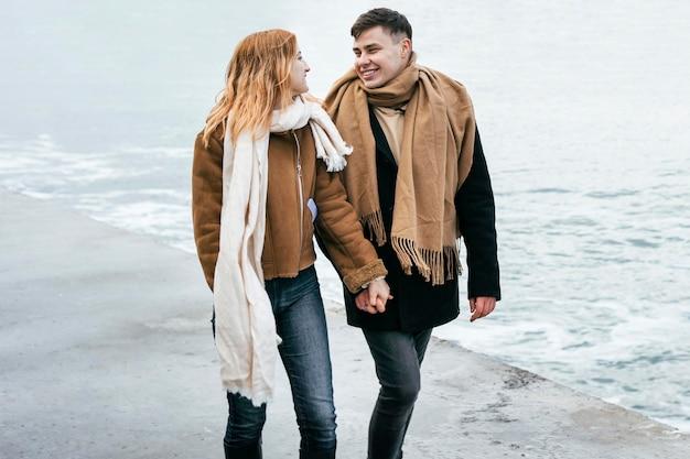 Vista frontal de la pareja caminando tomados de la mano por la playa en invierno