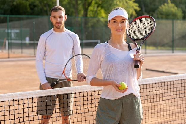 Vista frontal pareja en cancha de tenis