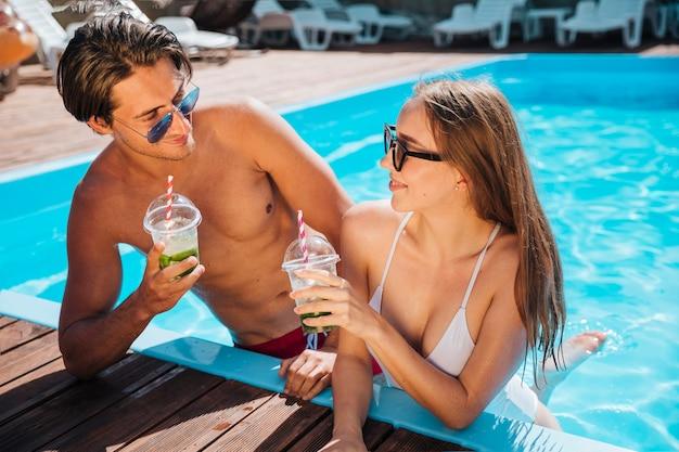 Vista frontal pareja disfrutando de sus cócteles.