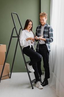 Vista frontal de la pareja haciendo planes para redecorar la casa