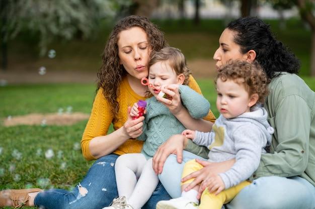 Vista frontal de la pareja lgbt al aire libre con niños en el parque