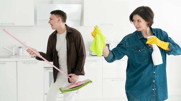 Vista frontal de la pareja limpiando la casa