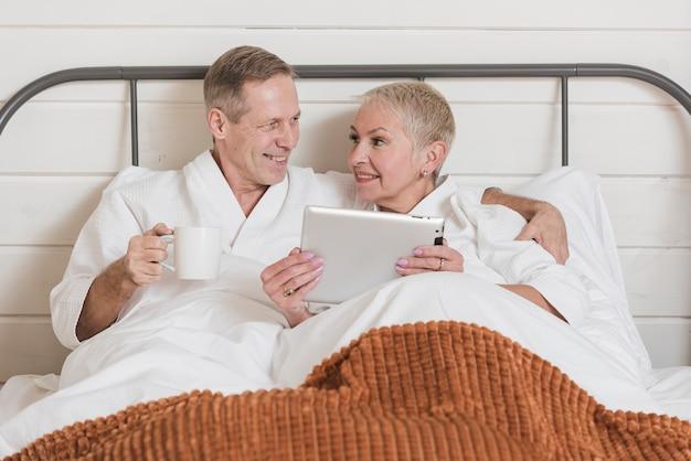 Vista frontal pareja madura mirando en una tableta en la cama