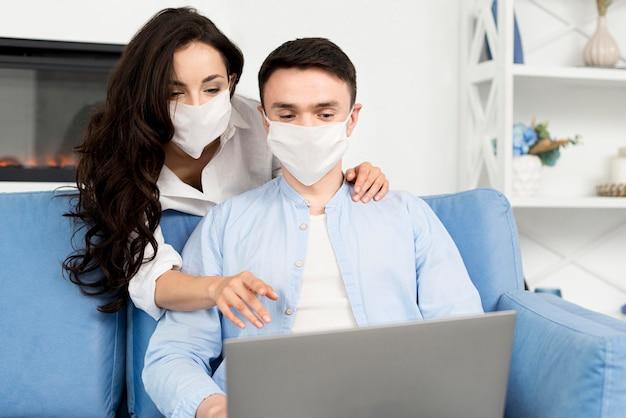 Vista frontal de la pareja con mascarillas en casa en la computadora portátil