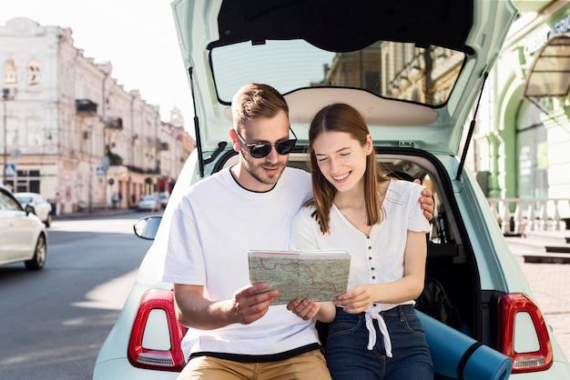 Vista frontal de la pareja mirando el mapa