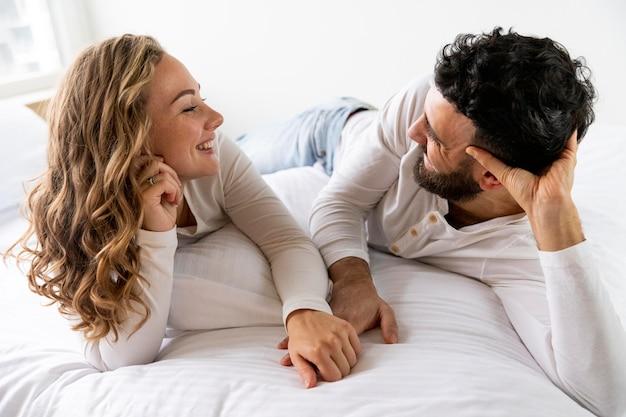 Vista frontal de la pareja romántica en la cama en casa