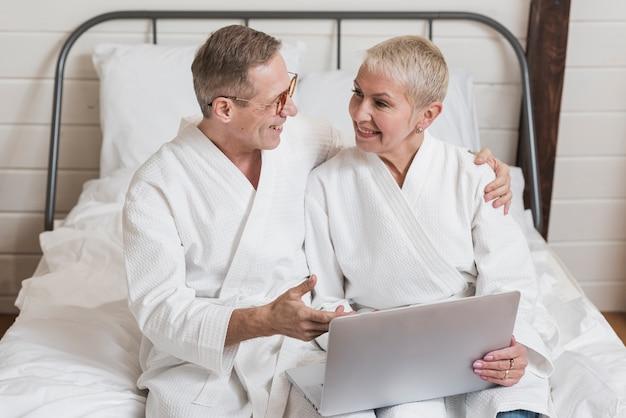Vista frontal pareja senior mirando en una computadora portátil en la cama juntos