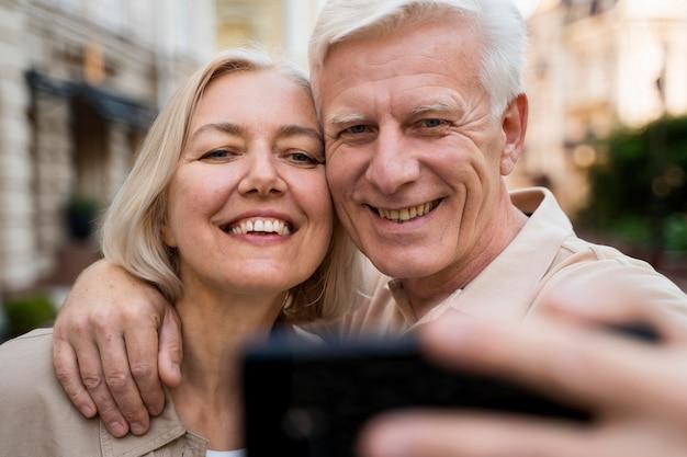 Vista frontal de la pareja senior sonriente tomando un selfie mientras está en la ciudad