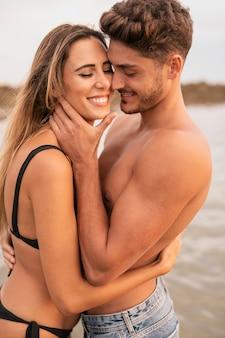 Vista frontal de la pareja sonriendo y abrazando
