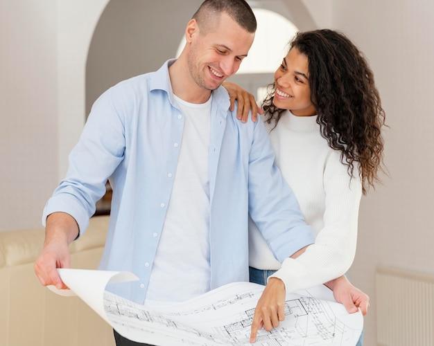 Vista frontal de la pareja sonriente sosteniendo planes de casa