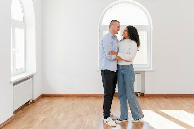 Vista frontal de la pareja sonriente en su nueva casa vacía con espacio de copia