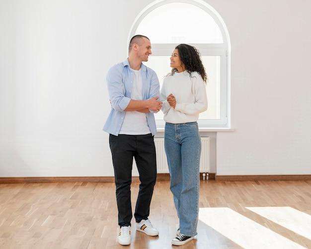 Vista frontal de la pareja sonriente en su nueva casa vacía