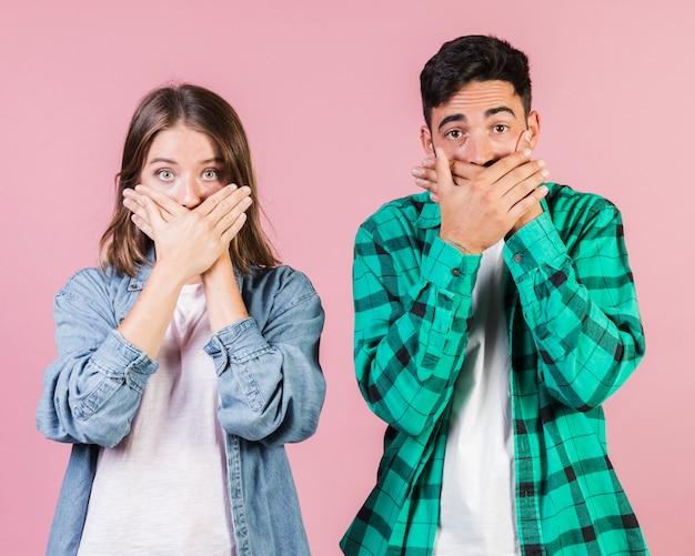 Vista frontal pareja sorprendida cubriendo sus bocas