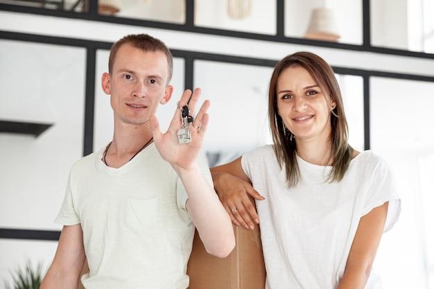 Vista frontal pareja sosteniendo una llave para su nueva casa