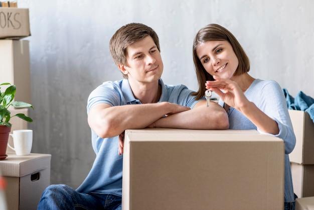 Vista frontal de la pareja sosteniendo las llaves de la nueva casa mientras empaca para mudarse