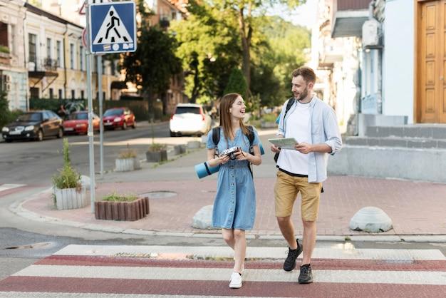 Vista frontal de la pareja de turistas con mapa y cámara en el cruce de peatones