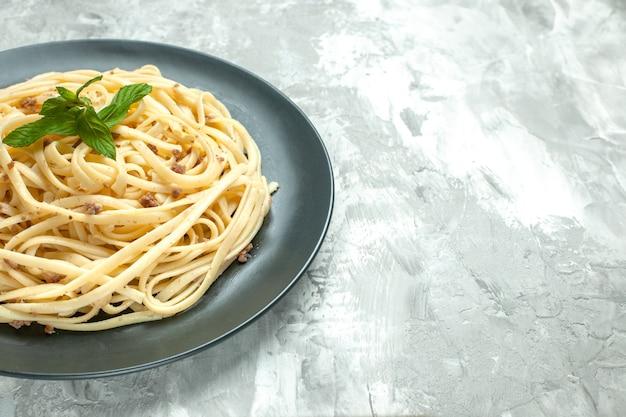 Vista frontal de la pasta italiana cocida dentro de la placa sobre fondo blanco.