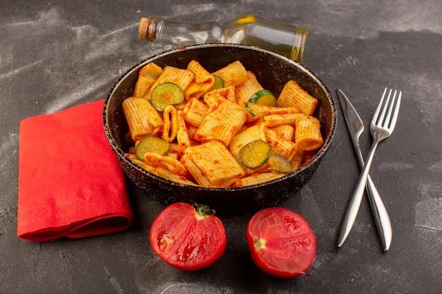 Una vista frontal de pasta italiana cocida con salsa de tomate y pepino dentro de la sartén sobre la superficie oscura