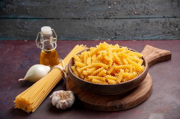 Vista frontal de la pasta italiana cruda con cebollas en el espacio oscuro