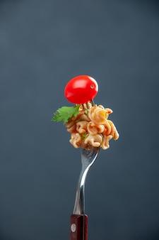 Vista frontal de pasta rotini con tomate cherry en un tenedor en el espacio libre de superficie aislada gris