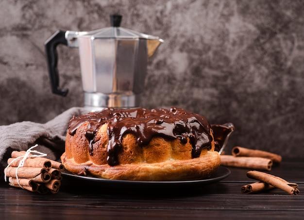 Vista frontal del pastel con cobertura de chocolate y palitos de canela