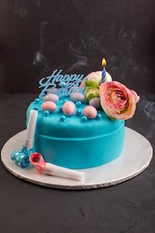 Vista frontal de un pastel de cumpleaños azul con flores en el color de la torta superior