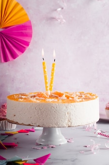 Vista frontal del pastel de cumpleaños con velas encendidas