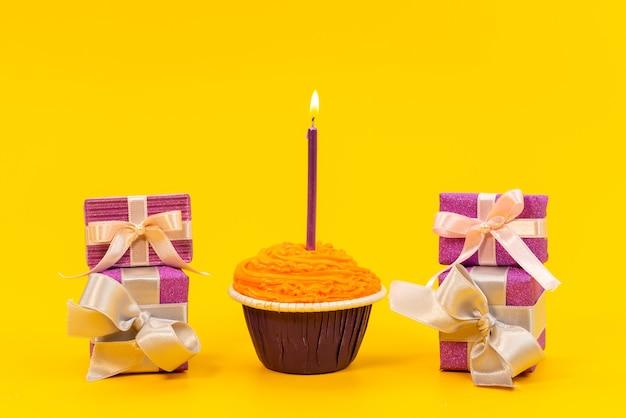 Vista frontal de un pastel de naranja con velas y cajas de regalo de color púrpura en amarillo, fiesta de cumpleaños de galletas