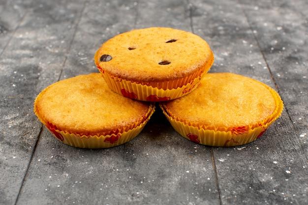 Vista frontal pasteles deliciosos redondos en el rústico fondo de madera gris