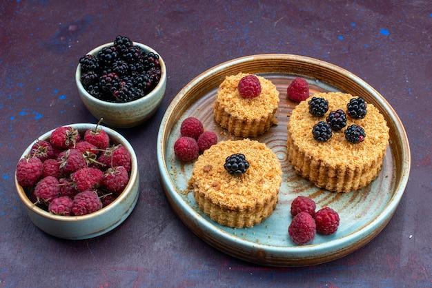 Vista frontal de pasteles dulces y deliciosos con bayas frescas sobre superficie oscura