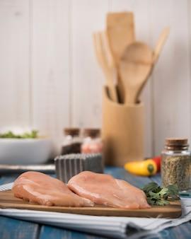 Vista frontal pechuga de pollo sobre tabla de madera con ingredientes