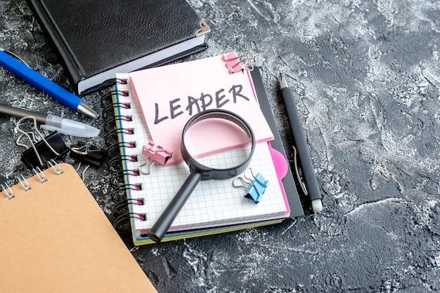 Vista frontal pegatina rosa con nota escrita de líder, bolígrafo y cuadernos sobre superficie gris, trabajo, escuela de negocios, colegio, oficina de fotografía en color