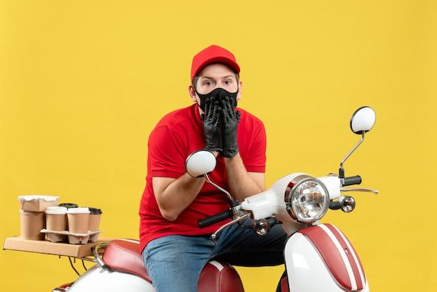 Vista frontal del pensamiento adulto joven vistiendo blusa roja y guantes de sombrero en máscara médica entregando orden sentado en scooter sobre fondo amarillo