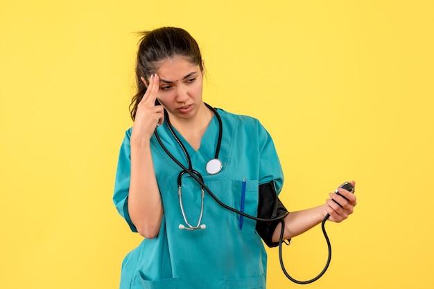 Vista frontal, pensamiento, doctora, en, uniforme, tenencia, esfigmomanómetros, posición, en, fondo amarillo
