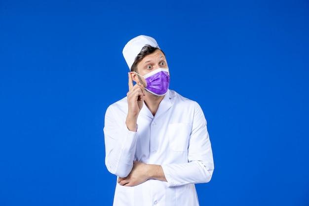 Vista frontal del pensamiento médico masculino en traje médico y máscara púrpura sobre azul