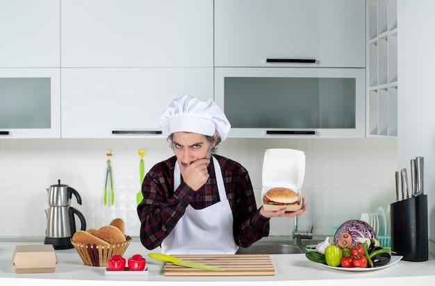 Vista frontal pensando en chef masculino sosteniendo una hamburguesa en la cocina moderna