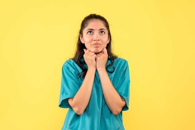 Vista frontal pensando en doctora en uniforme de pie sobre fondo amarillo aislado