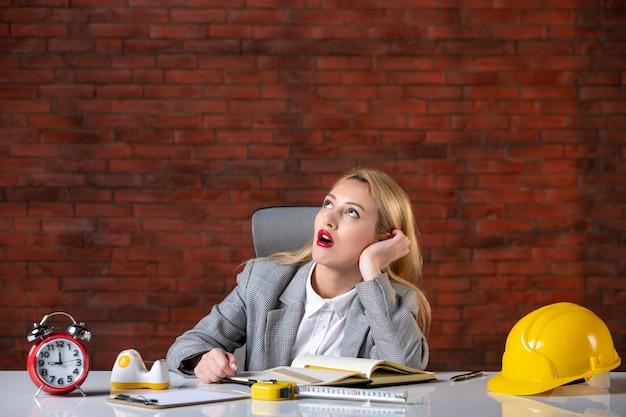 Vista frontal pensando en ingeniera sentada en la oficina