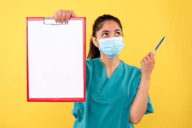 Vista frontal pensando mujer médico en uniforme sosteniendo portapapeles rojo y bolígrafo de pie sobre fondo amarillo