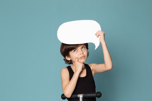 Una vista frontal pensando niño niño con cartel blanco en camiseta negra en el espacio azul