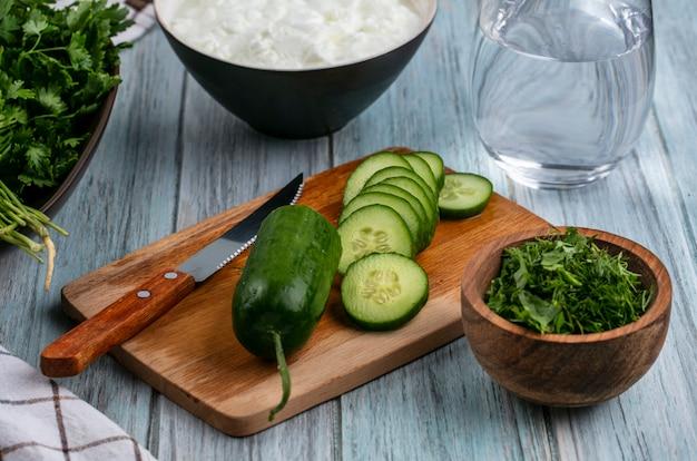 Vista frontal de pepinos en rodajas en una pizarra con un cuchillo y verduras sobre una superficie gris