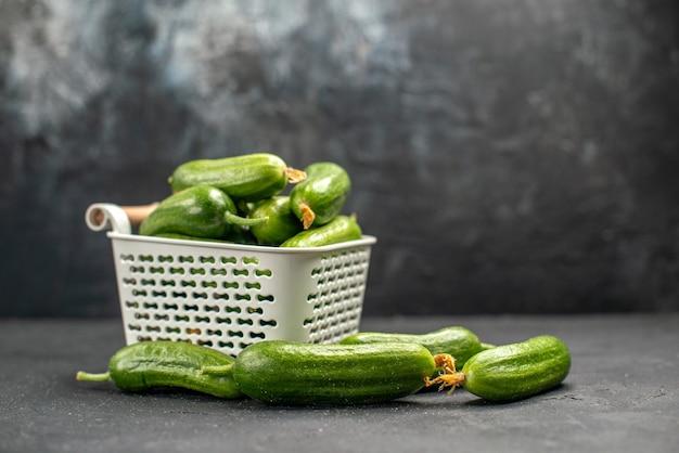 Vista frontal de los pepinos verdes frescos dentro de la cesta sobre fondo oscuro alimentos saludables foto ensalada color comida