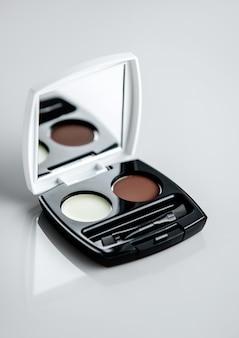 Una vista frontal pequeña caja de rubores cosméticos con pequeño espejo en el escritorio blanco
