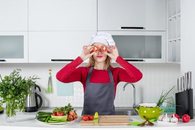 Vista frontal pequeña cocinera en delantal poniendo tomates delante de sus ojos