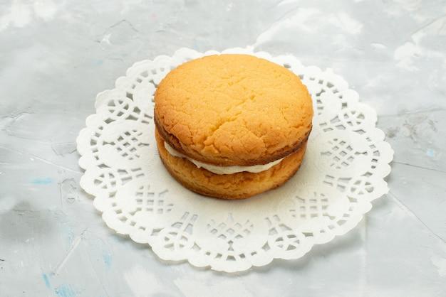Vista frontal pequeña galleta redonda simple y deliciosa galleta de crema sándwich en la superficie de luz gris galleta