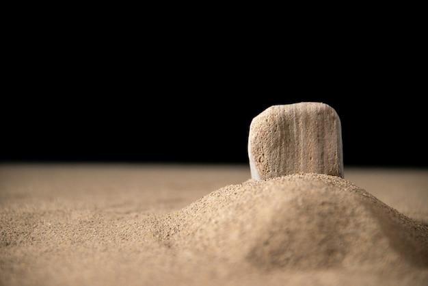 Vista frontal de la pequeña luna tumba sobre arena.