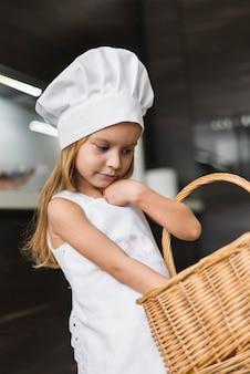 Vista frontal de la pequeña niña chef llevando una cesta de mimbre