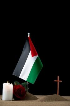 Vista frontal de la pequeña tumba con bandera palestina en negro